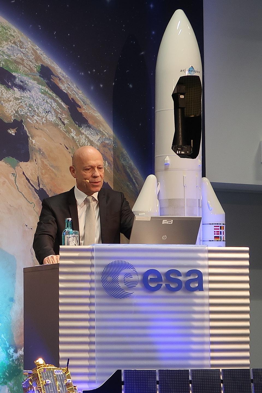 Dr. Rolf Densing steht an einem Pult, im Hintergrund steht ein Raketenmodell