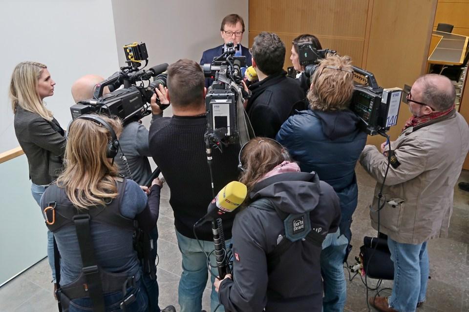 Neun Fernsehjournalisten stehen mit Mikrofonen und Kamera im Viertelkreis vor einem Oberstaatsanwalt