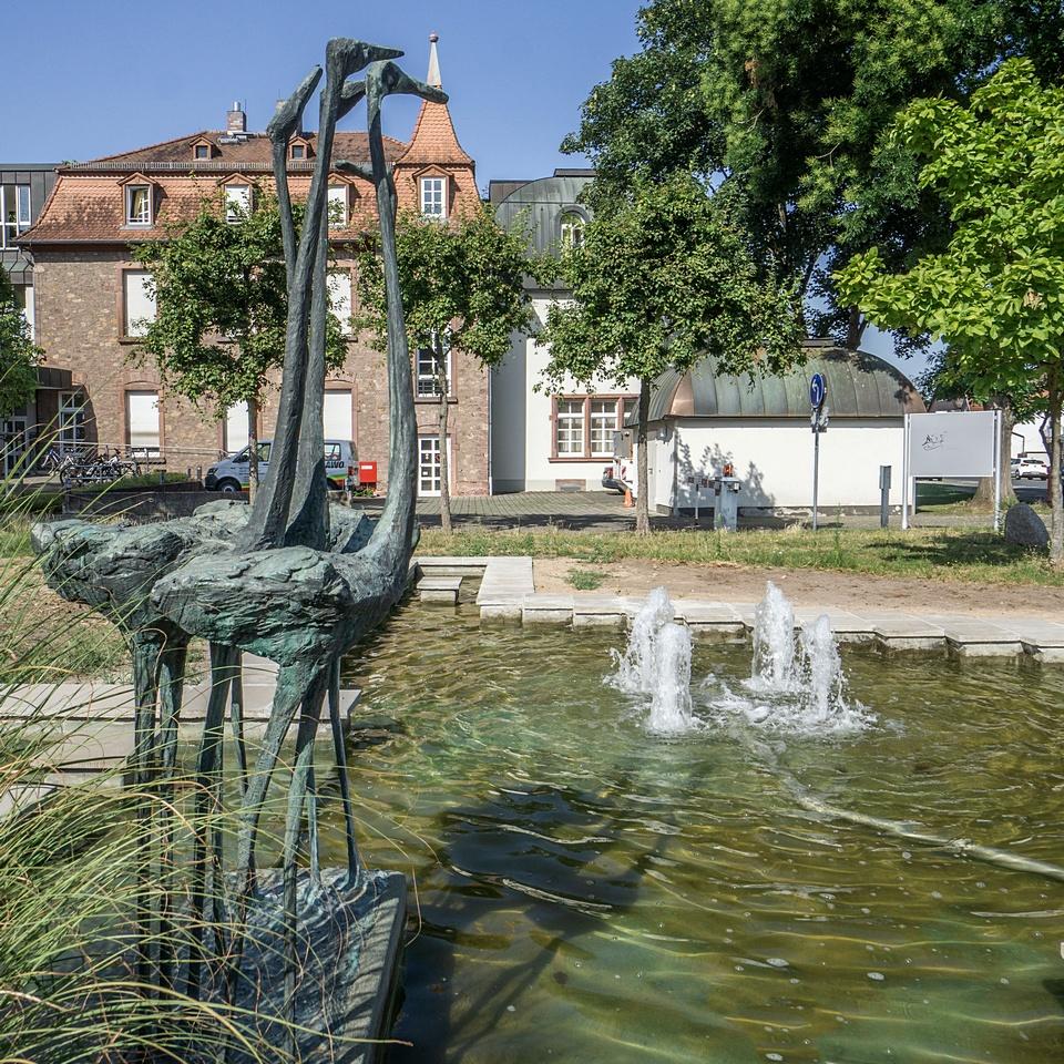 Brunnen mit vier Fontainen und Flamingo-Skulpturen, dahinter das Ohlystift in Gräfenhausen