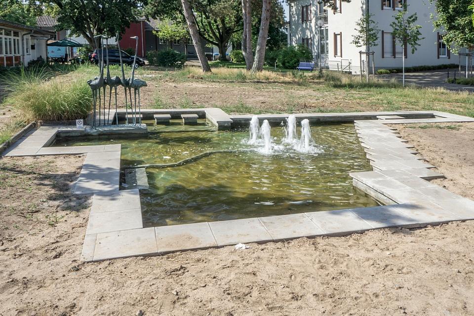 Der Brunnen zwischen Bürgerhaus Gräfenhausen und Ohlystift in der totalen mit Flamingo- Skulpturen und vier Fontainen.