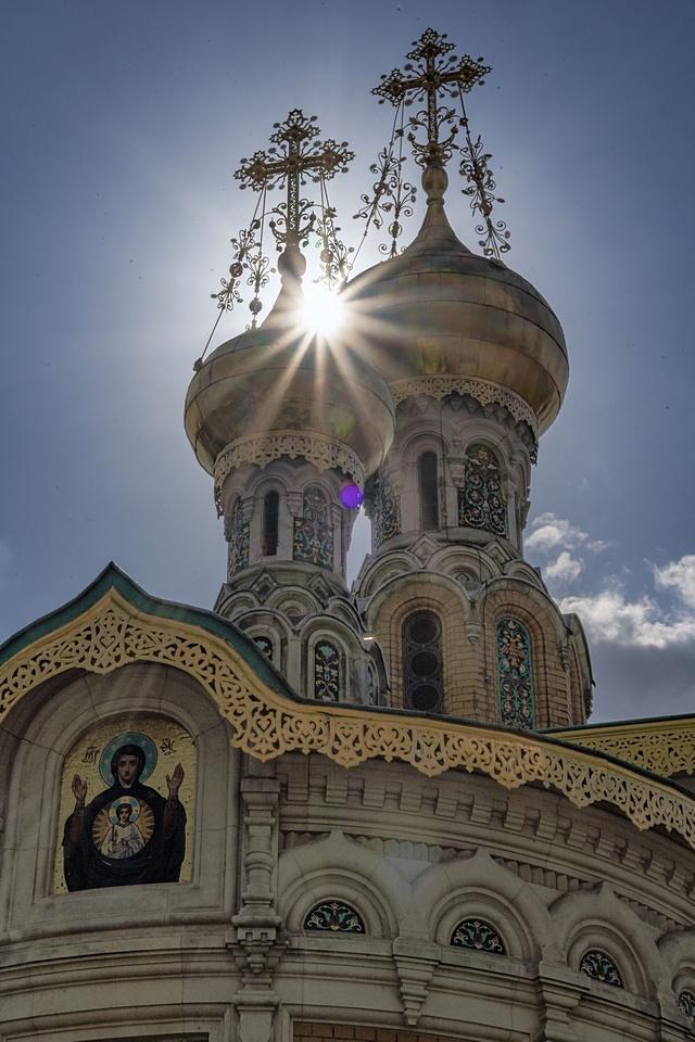 Die Türme der Russischen Kapelle auf der Mathildenhöhe im Gegenlicht. Die Sonne scheint zwischen den Türmen durch.