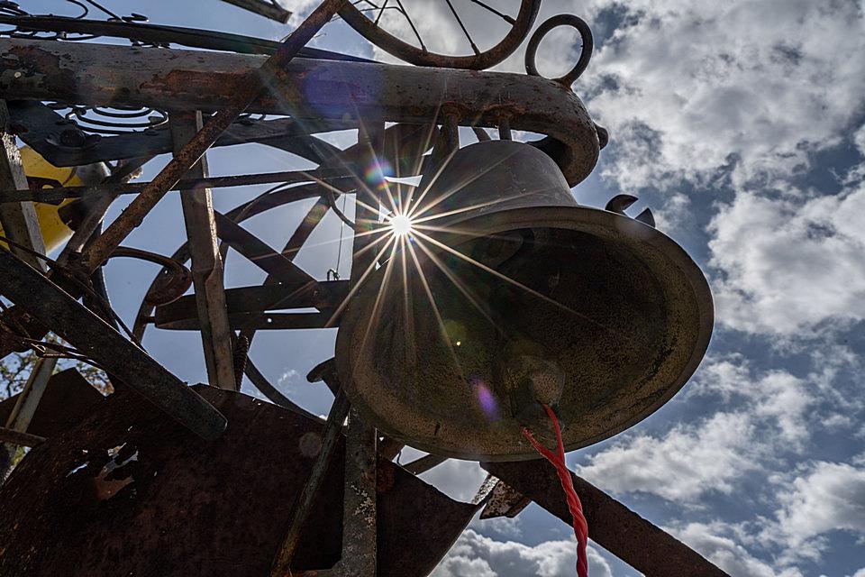 Eine Glocke neben der die Sonne als Blendenstern durchsticht.