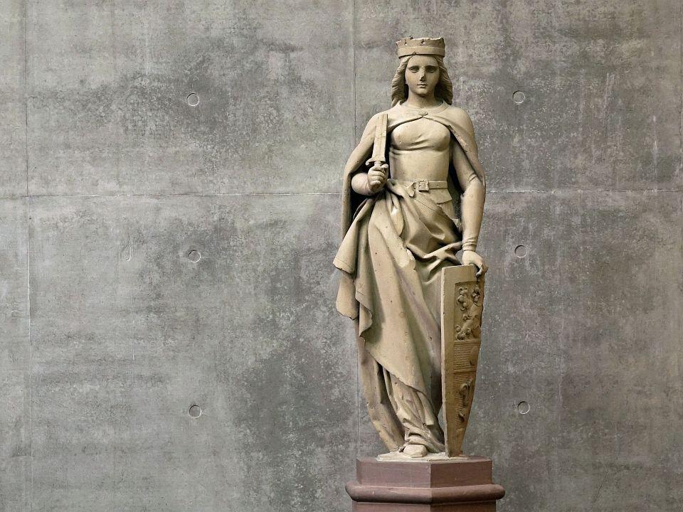 Die Darmstadtia-Figur vor Sichtbeton im Darmstadtium
