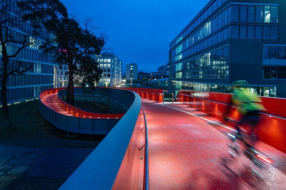 Die Fahrradfahrer- und Fußgängerbrücke über die Rheinstraße. Mit Beleuchtung zur Blauen Stunde.