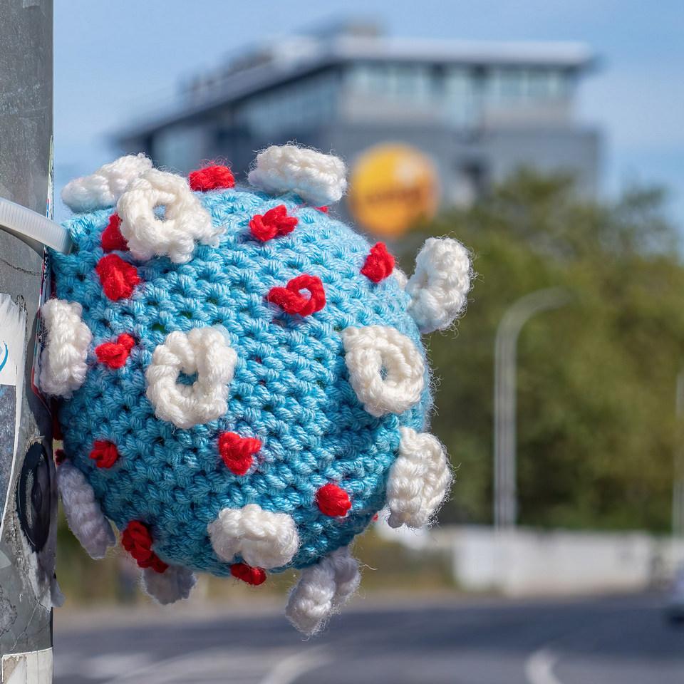 gehäkeltes Coronavirus an einem Ampelpfahl in der Kasinostraße